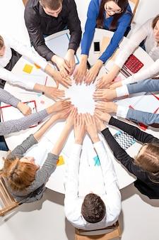 Team sitzt hinter dem schreibtisch, prüft berichte, spricht und verbindet die hände miteinander. draufsicht. geschäftskonzept der zusammenarbeit, teamarbeit, besprechung