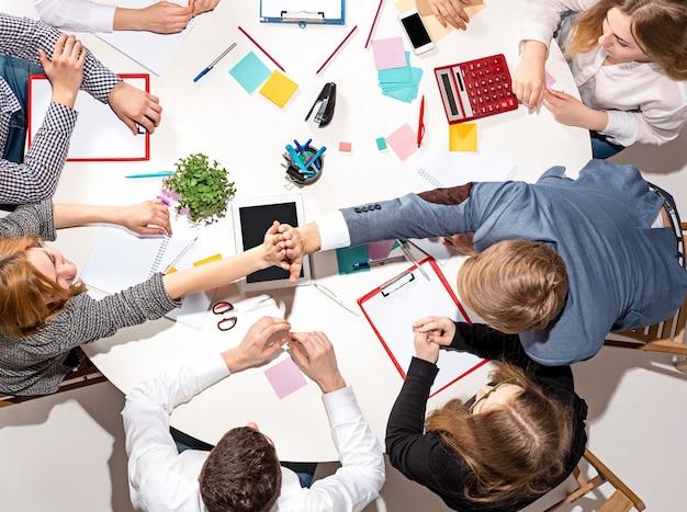 Team sitzt hinter schreibtisch, überprüft berichte, redet. ansicht von oben. das geschäftskonzept der zusammenarbeit, teamarbeit, meeting