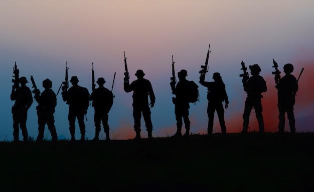 Team spezialeinheiten. soldat sturmgewehr mit schalldämpfer. silhouette action soldaten halten waffen. militär- und gefahrenkonzept.