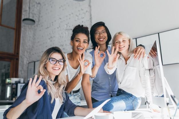 Team talentierter junger webentwickler, die mit einem harten projekt fertig sind und mit einem lächeln posieren