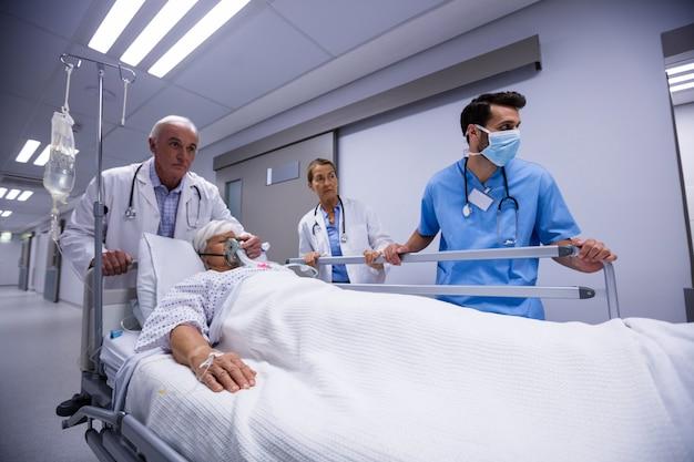 Team von ärzten, die ältere frau zum operationssaal bringen