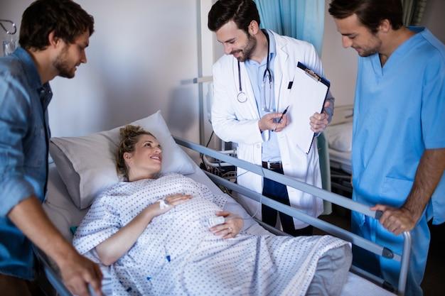 Team von ärzten, die mit der schwangeren frau interagieren