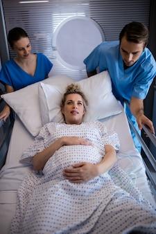 Team von ärzten, die schwangere frau zum operationssaal bringen