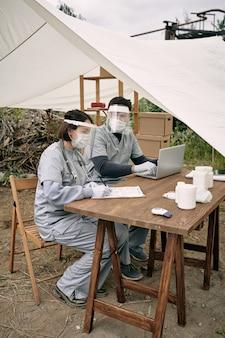 Team von ärzten in sicherheitsgesichtsschutz, die am tisch im zelt sitzen und mit krankenkarten von flüchtlingen in abgelegenen gebieten arbeiten