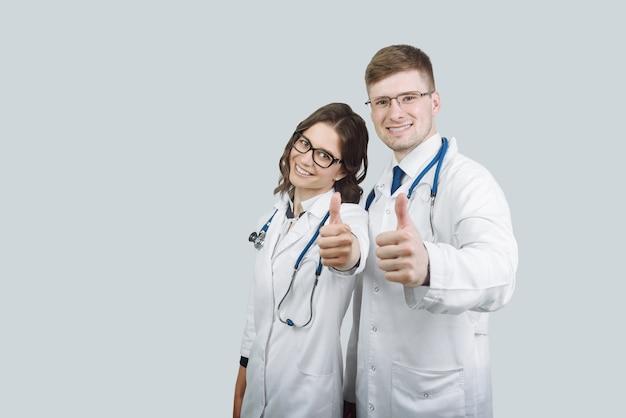 Team von ärzten mann und frau zeigt ok zeichen mit daumen nach oben. erfolg und ein hohes serviceniveau im gesundheitswesen