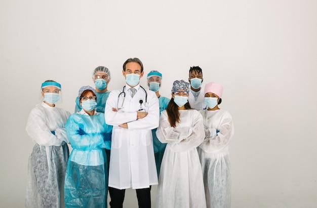 Team von ärzten und krankenschwestern, die einwegschutzanzüge und gesichtsmasken tragen, um covid19 zu bekämpfen
