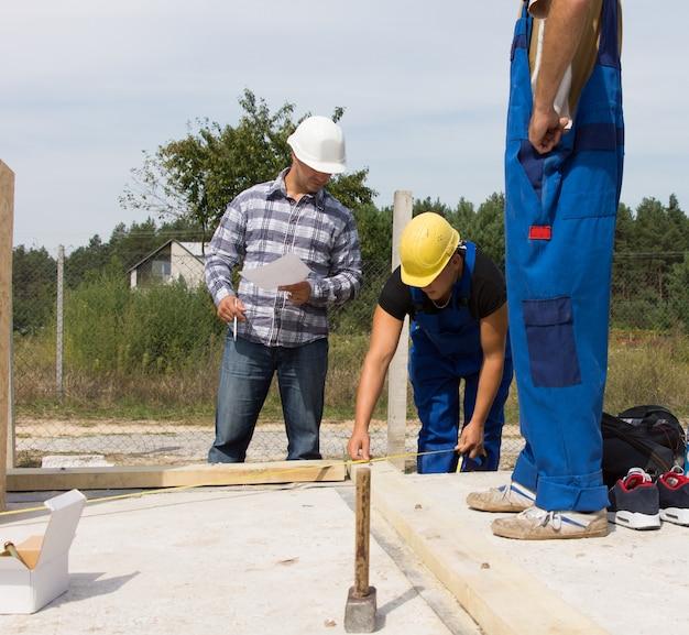 Team von arbeitern auf einer baustelle für ein neues haus, das stützbalken für die wanddämmung misst