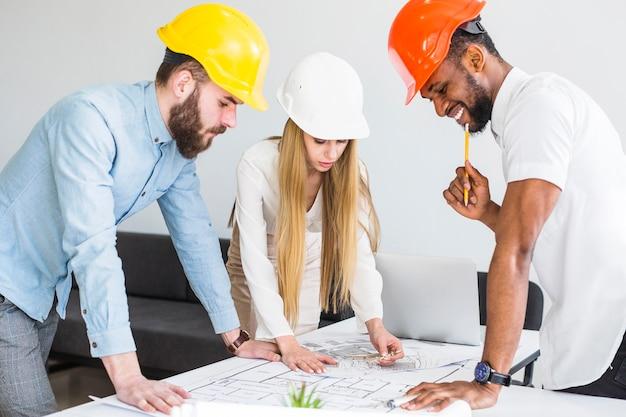 Team von architekten, die an bauplan arbeiten