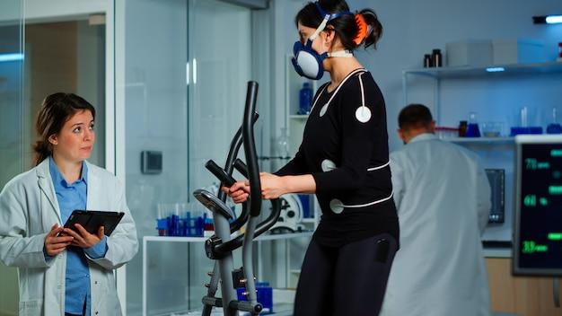 Team von arztforschern, die die ausdauer von frauenleistungssportarten überwachen, die eine maske tragen, die crosstrainer läuft. laborwissenschaftsarzt, der vo2 der sportlerin misst und tablette hält, die den gesundheitszustand erklärt