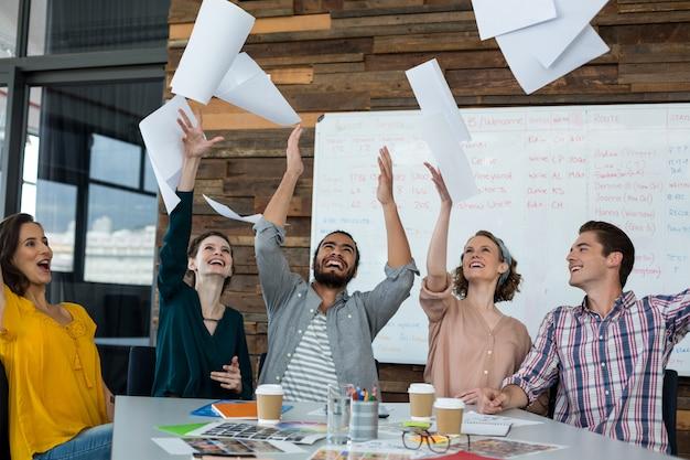 Team von aufgeregten grafikdesignern, die während des treffens dokumente in die luft werfen