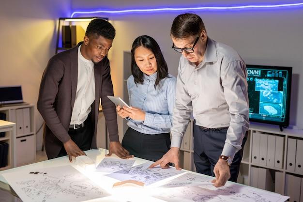 Team von automobilingenieuren diskutiert autoskizzen