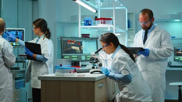 Team von biochemie-wissenschaftlern, die medikamente gegen neue viren entwickeln, arzt, der proben überprüft, während krankenschwester notizen in der zwischenablage in einem modern ausgestatteten labor macht. multiethnische wissenschaftler arbeiten