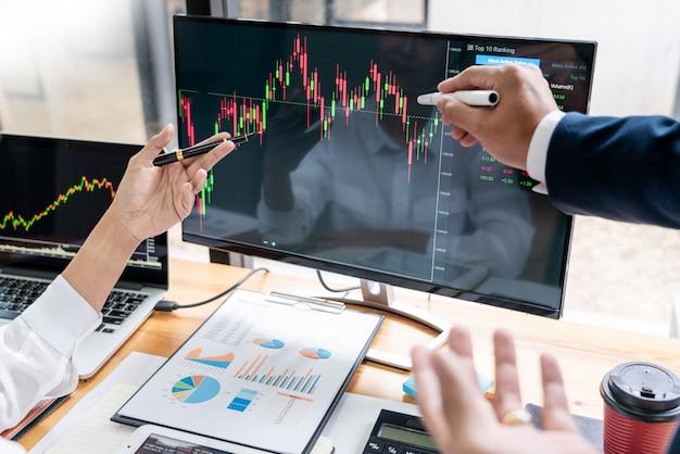 Team von börsenmaklern, die mit bildschirmen sich besprechen