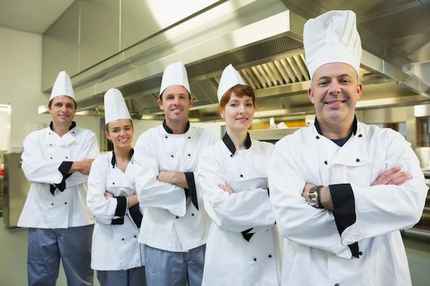 Team von chefs, die an der kamera lächeln