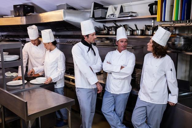 Team von chefs, die zusammen in der handelsküche stehen