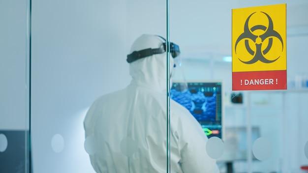 Team von chemikern, die einen schutzanzug tragen und im gefahrenbereich des medizinischen forschungslabors arbeiten. wissenschaftler untersuchen die entwicklung von impfstoffen mit hightech für die erforschung der behandlung des covid19-virus