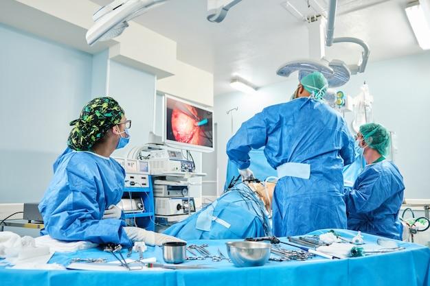 Team von chirurgen, die laparoskopische operationen in einem operationssaal durchführen