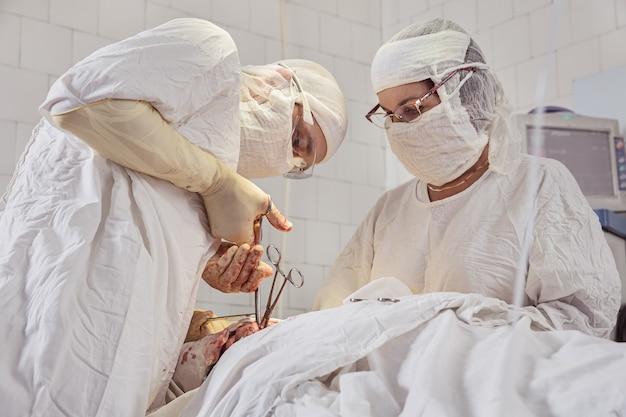 Team von chirurgen in form führt eine operation am patienten in der klinik für plastische chirurgie maxillofazial durch