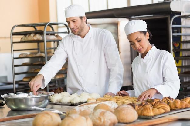 Team von den bäckern, die teig und gebäck vorbereiten