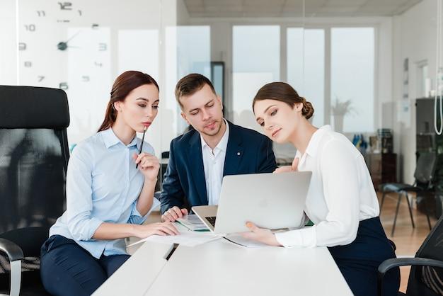 Team von den fachleuten, die laptop betrachten und geschäft im büro besprechen