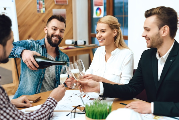 Team von designerarchitekten, die champagner gießen.