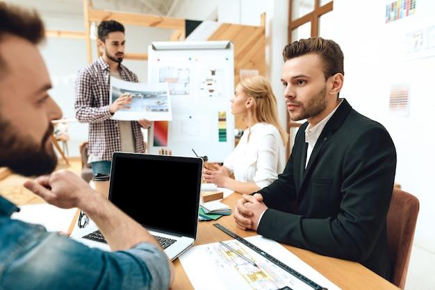 Team von designern architekten präsentation beobachten