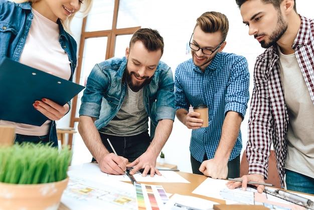 Team von designern architekten zeichnen auf blaupause