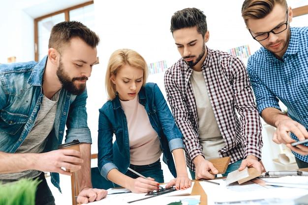 Team von designern architekten zeichnen auf blaupause.