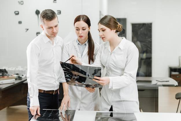 Team von doktoren, die röntgenstrahl eines patienten überprüfen