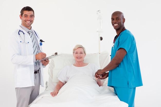 Team von doktoren mit einem patienten lächelnd an der kamera