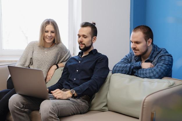 Team von drei personen, die am laptop im büro auf dem sofa arbeiten