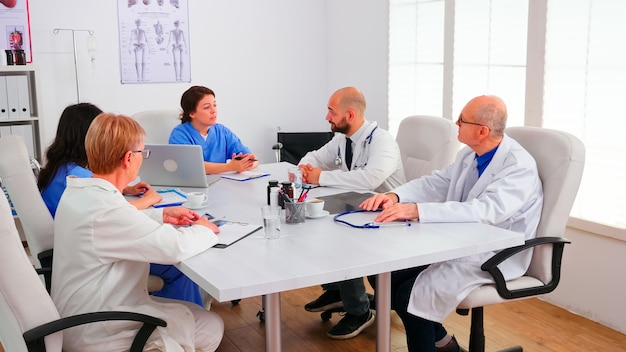 Team von erfahrenen ärzten, die am schreibtisch im konferenzraum des krankenhauses sitzen und eine einweisung haben. klinikfachtherapeut im gespräch mit kollegen über krankheiten zur behandlungsentwicklung, mediziner medicine