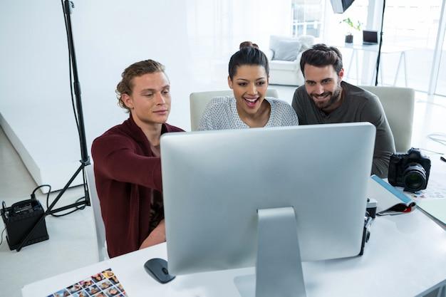 Team von fotografen, die über computer am schreibtisch arbeiten