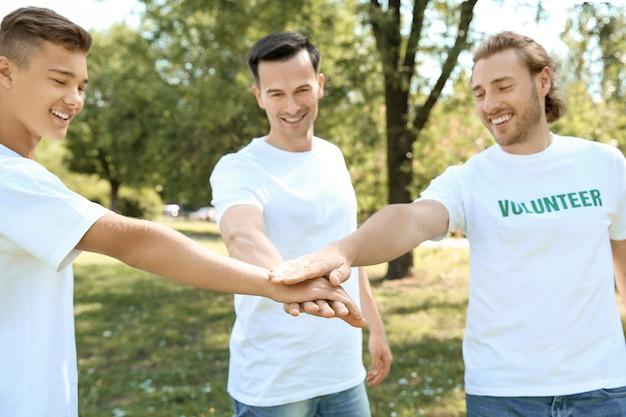 Team von freiwilligen, die im freien die hände zusammenstellen