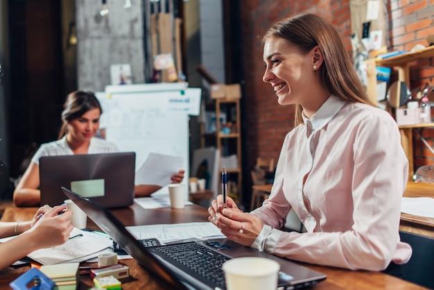Team von geschäftsfrauen, die mit papieren arbeiten und laptops verwenden, die am schreibtisch im büro sitzen.
