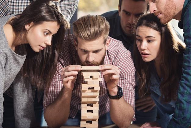 Team von geschäftsleuten im büro bauen eine holzkonstruktion. konzept der teamarbeit, partnerschaft und unternehmensgründung