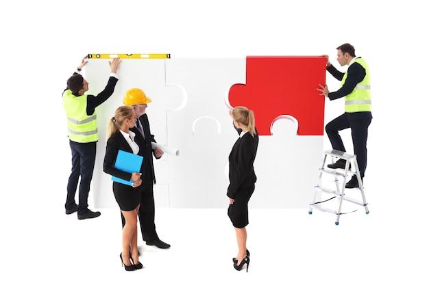 Team von geschäftsmann und arbeitern, die zusammen auf weißem hintergrund ein puzzle zusammenbauen