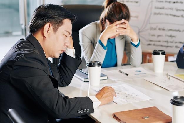 Team von gestressten und müden geschäftsleuten, die nach einer globalen pandemie suchen, um die wirtschaftskrise besser zu überstehen