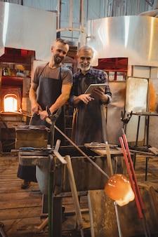 Team von glasbläsern, die digital arbeiten, während sie über einem geschmolzenen glas arbeiten