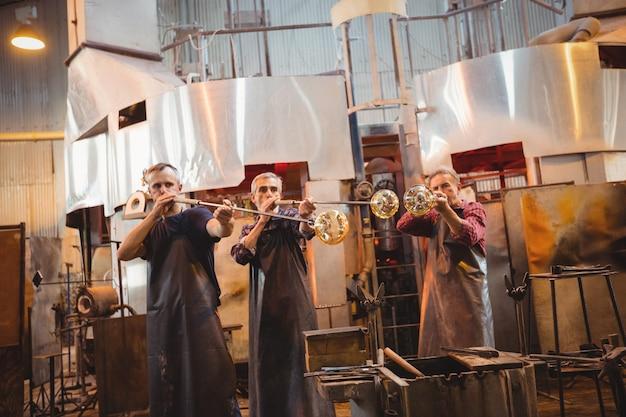 Team von glasbläsern, die ein glas auf dem blasrohr formen