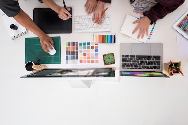 Team von grafikdesignern, die an einem computer im officeideas-kreativen besetzungs-design-studio, künstlerarbeitsplatz mit draufsicht arbeiten.