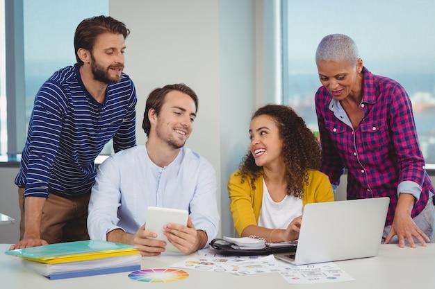 Team von grafikdesignern diskutiert über laptop