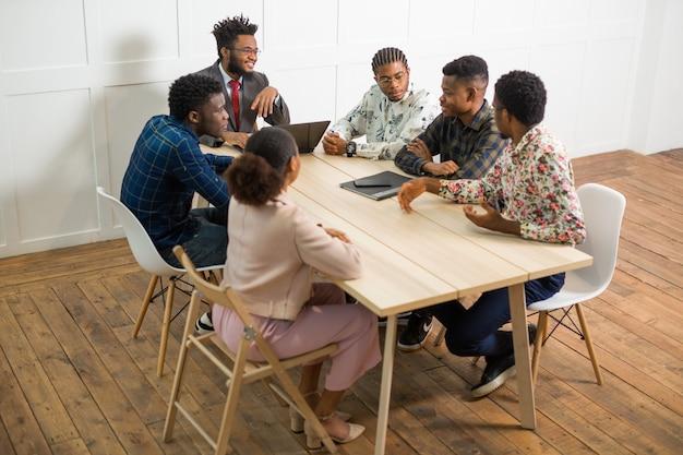 Team von jungen afrikanischen leuten, die im büro am tisch mit laptop arbeiten