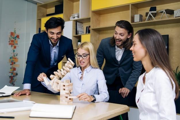 Team von jungen geschäftsleuten bauen eine hölzerne konstruktion auf