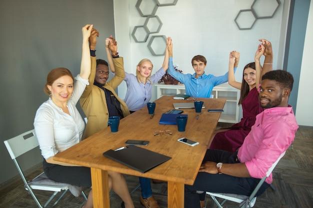 Team von jungen schönen menschen im büro mit den händen nach oben