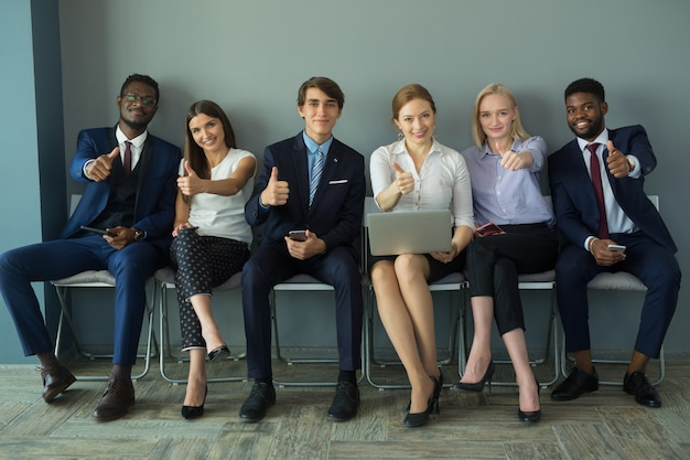 Team von jungen schönen menschen im büro mit handbewegung