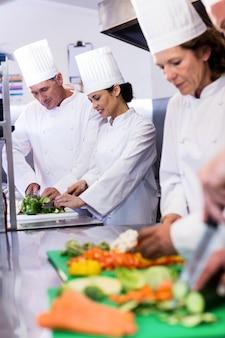 Team von köchen, die gemüse hacken