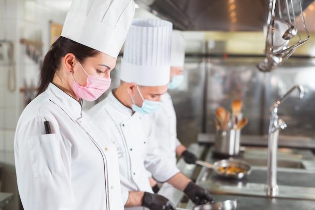 Team von köchen, die in einem restaurant kochen