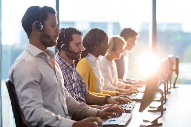 Team von kollegen, die an ihrem schreibtisch mit headset arbeiten