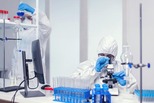 Team von medizinern in einem modernen labor, das nach einem coronavirus-impfstoff mit ppe sucht. chemikerforscher während der globalen pandemie mit covid-19-prüfprobe im biochemielabor